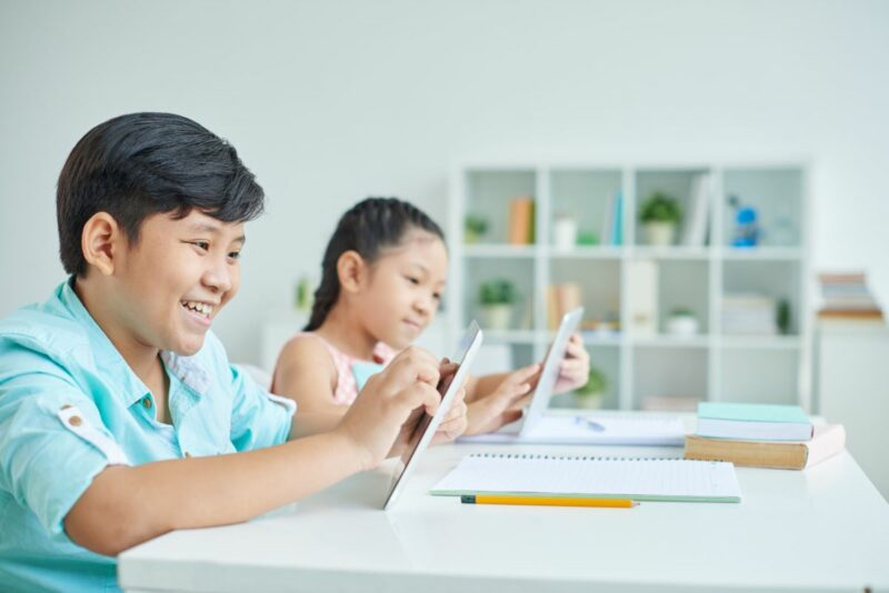 Vietnamese Boy And Girl Using Digital Tablet In Class